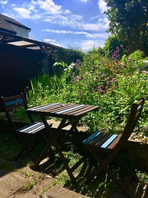 A table and chair hidden amongst the bushes of the finest garden in Abergavenny