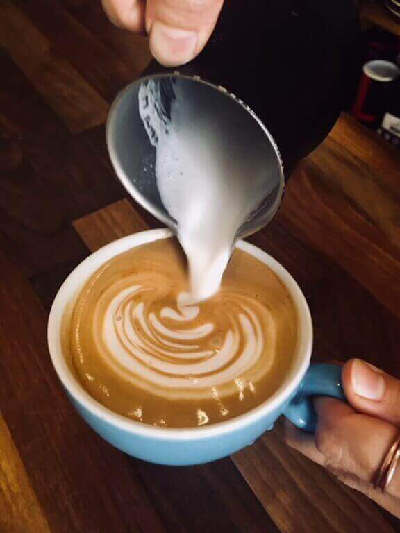 Latte art being poured into the coffee cup