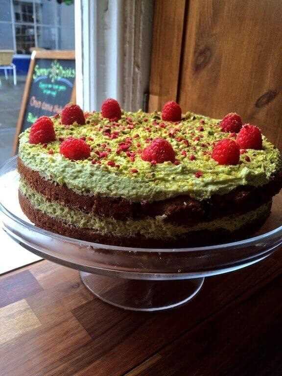 A double layer cake made with pistachios and with raspberries on top