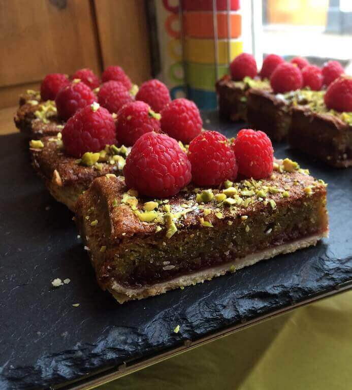 Tart with pistachios and raspberries covering it